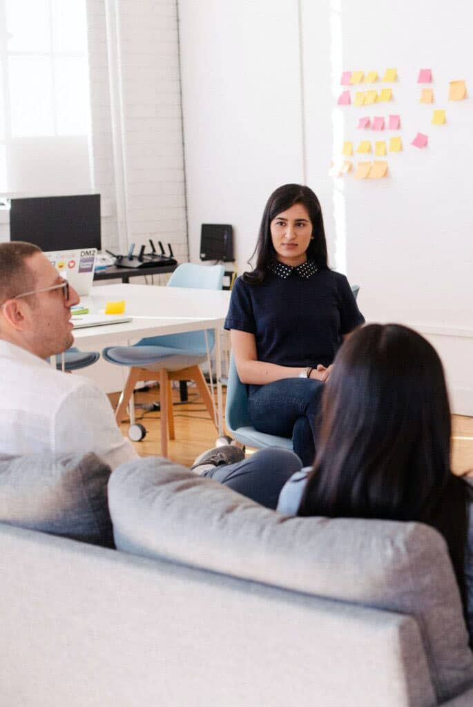 Office workers discussing the Google workspace training information provided by Encompass Innovate in their modern office.